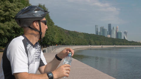 middle-aged man cycling helmet, wearing sunglasses, drinking water from a bottle Live Action