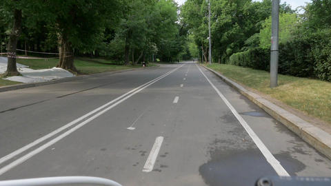 handlebars and bicycle front wheel speeding along road Footage