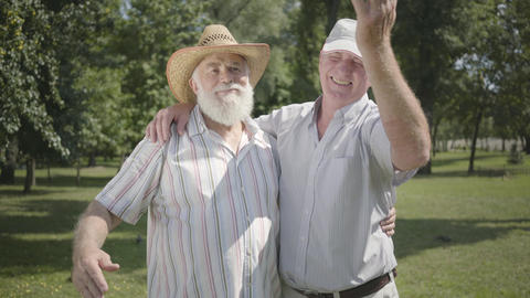 Two positive old men looking away inviting the third friend to join them in the Footage