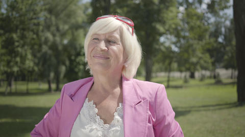 Mature smiling woman looking at camera smiling standing in summer park. Leisure Live Action