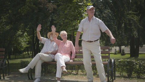 Two senior men and one woman waving hands while their friend woman driving on Footage