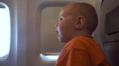 4k - The baby is trying to open the curtain window in the plane Archivo