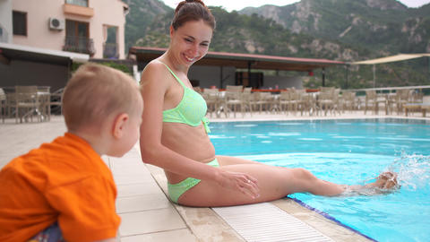 4k - Girl sits, plunging her feet into the pool, outside her son is watching Footage