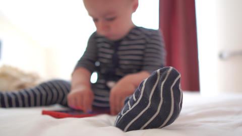 4k - Blurred child clicks on the screen of the phone, sitting on the bed Footage