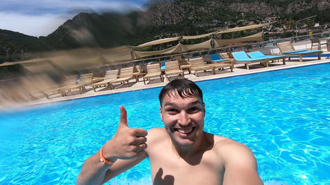 Young guy dives into the pool with an action camera and shows the ok gesture Live Action