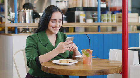 girl texts on cellphone sitting at table in light cafeteria Live Action