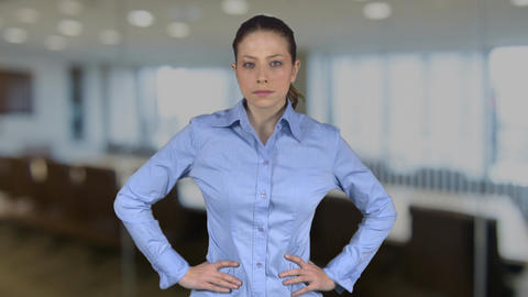 Confident professional female with hands on hips in an office Footage