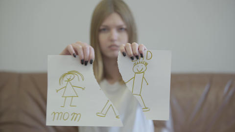 Portrait of sad young woman tearing apart children's drawing with the image of Footage
