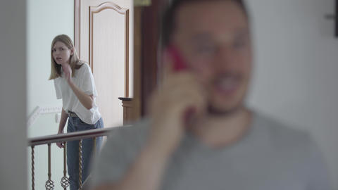 Portrait of happy man talking with his paramour by cellphone while his wife Live Action