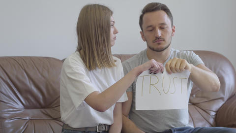 Man and woman tearing apart the word trust written on the paper. Problems in the Footage