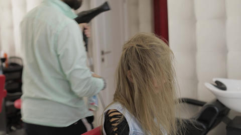 Professional hairdresser styling blows lacquer on model hair with a hair dryer Footage