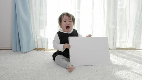 Crying kid with sketchbook Live Action