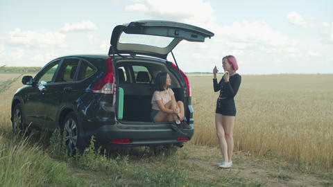 Carefree diverse females chatting during road trip Live Action