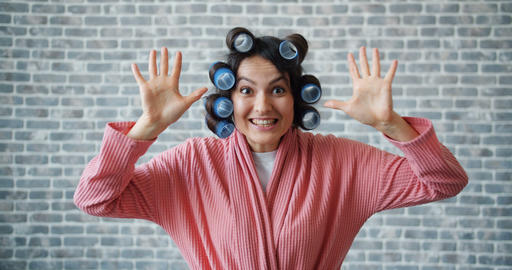 Portrait of funny girl with hair curlers playing hide and seek hiding eyes Live Action