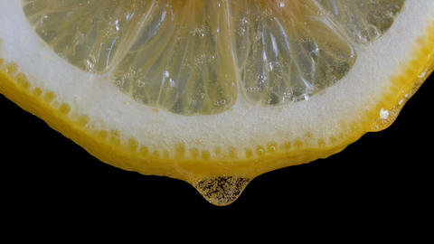 Honey pouring on half slice cut of fresh lemon against black background GIF