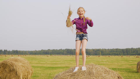 Playful girl dancing on hay stack with straw in hands at harvesting field Live Action
