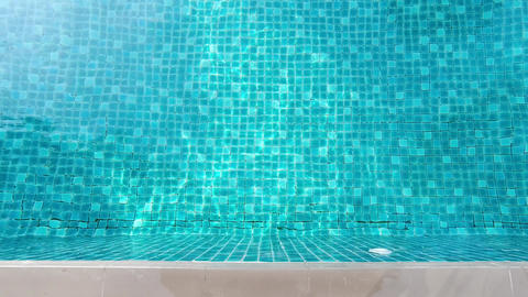 Swimming pool blue water and foot on edge in summer and white side bar floor tiles in hotel for ライブ動画