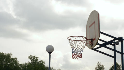 Throwing the ball into basketball hoop outdoor. Basketball player throwing ball Live Action