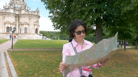 brunette woman looks at paper map against the background of a historic building Footage