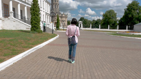 A middle-aged woman in a pink shirt and blue trousers walks around the historic Footage