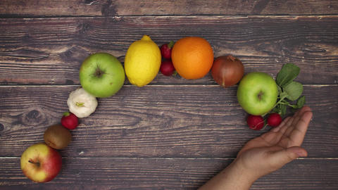 Man's hand moving on wooden background and fruits and vegetables appear - Stop motion Animation