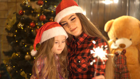 Two Charming Sisters In Holiday Hat With Sparkling Bengal Lights Live Action