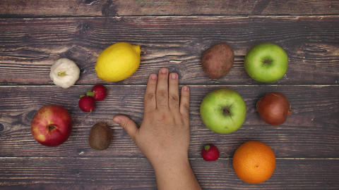 Man's hand strike on wooden background and fruits and vegetables appear - Stop motion Animation