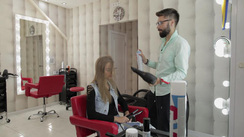 Professional hairdresser styling blows lacquer on model hair with a hair dryer Live Action