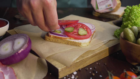 The cook adds sliced pickles to the sandwich with ham and vegetables on the Live Action