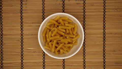 Fusili in a dish on wooden background - Stop motion Animation