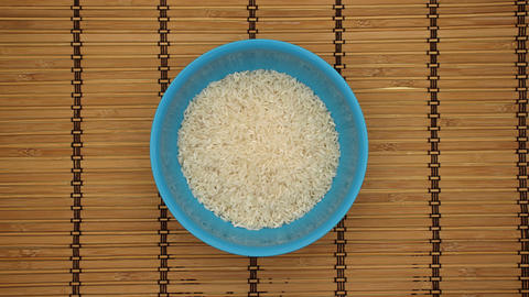 Rice in a blue dish on a wooden background - Stop motion Animation