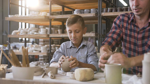 Caring father teaching little son how to work with clay on potters wheel Live Action