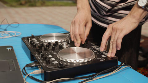 Close up DJ mixing music on sound console at outdoor party. Disc jockey playing Footage