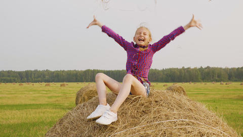 Carefree teenager girl scattering dry straw on countryside field. Happy girl Live Action