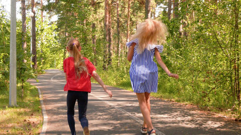 Two girlfriends running and jumping on pathway in green summer park Carefree Footage