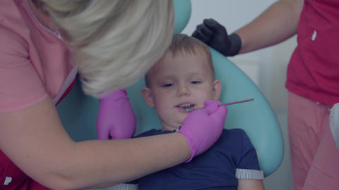 Dentist in medical mask and gloves checking tooths of little carefree boy Live Action