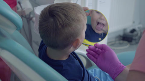 Gloved dentist hands checking the tooths of the little carefree boy sitting in Live Action