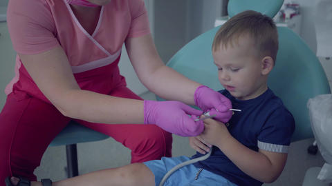 Dentist in medical mask and gloves ready to checking tooths of little carefree Live Action