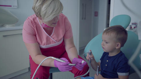 Dentist in medical mask and gloves ready to checking tooths of little carefree Footage