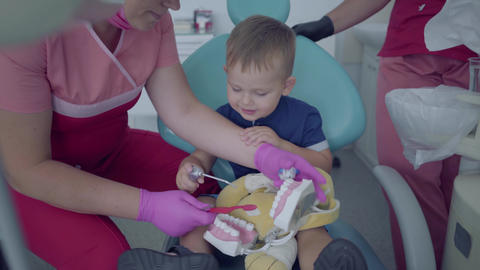 Cute little boy in the dentist office. The doctor teaching the little patient to Footage