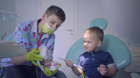 Teenage boy and his little brother playing in dentist office. Older brother Live Action
