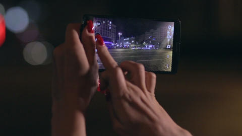 Woman takes photo of city in streetlights at night Footage