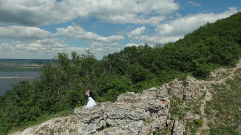 bride and groom kissing on the rock Footage