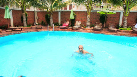 Bearded Old Man Laughs Dives Backward into Pool Footage