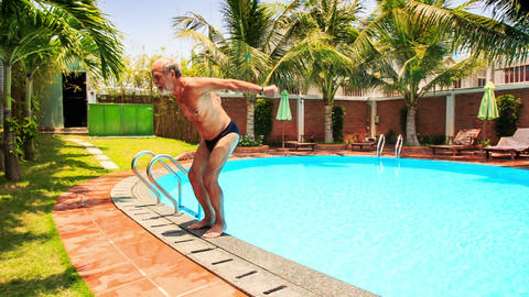 Bearded Old Man Dives Backward into Swimming Pool Footage