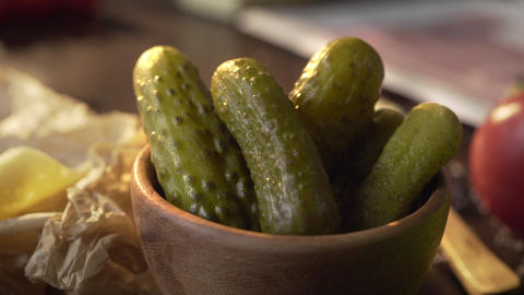 Pickles are in the wooden bowl on the kitchen table in a beam of sunset light Live Action