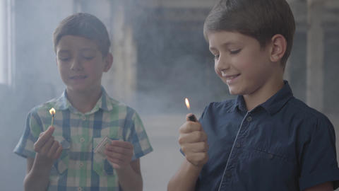 Two adorable boys in a smoky abandoned room. One boy with a burning match, the Live Action