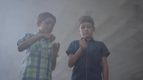Two little boys in a smoky abandoned room. One boy with a burning match, the Live Action