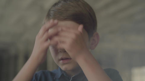 Close-up of confused scared boy standing in the smoky room holding head with Footage