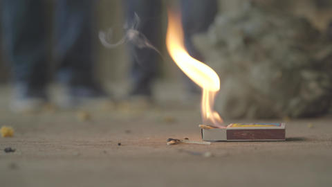 The matchbox burning on the floor, unrecognized kids running away. Concept of Live Action